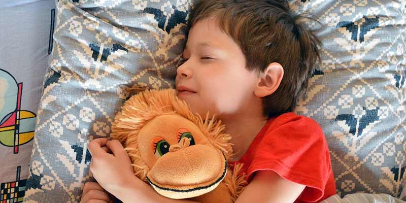Ребенок спит на подушке с игрушкой