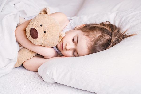 Ребеонк спит на матрасе с медведем